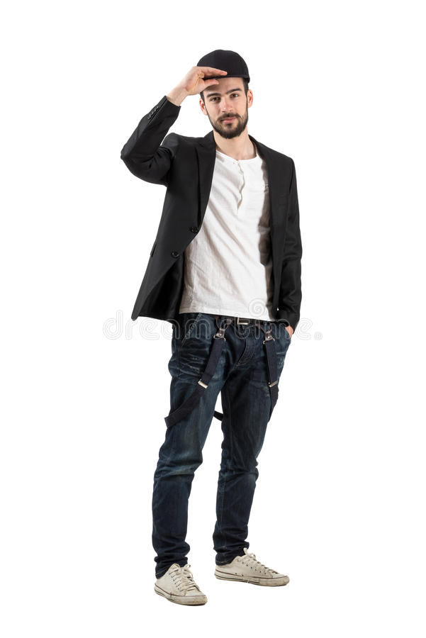 Young fashionable guy holding putting baseball cap on his head. Full body length portrait isolated over white background royalty free stock photo