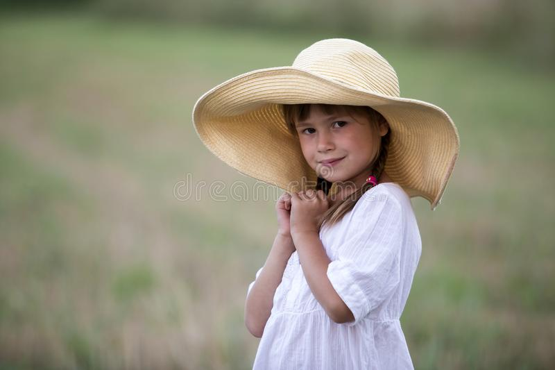 Young fashionable lovely cute girl with long braids in nice white summer dress and big straw hat. royalty free stock photography