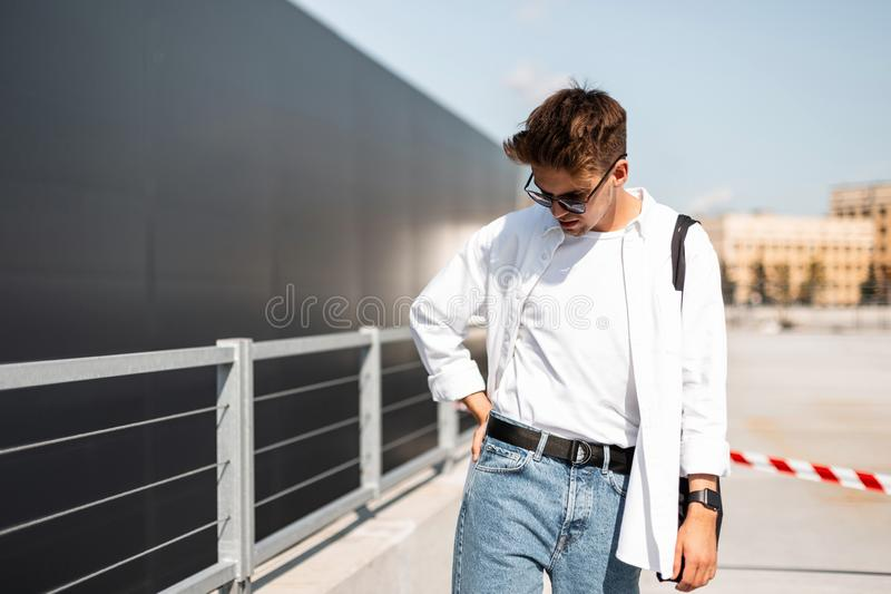 Young fashionable man model in a T-shirt in a white shirt in vintage blue jeans in sunglasses walks around the city royalty free stock photo