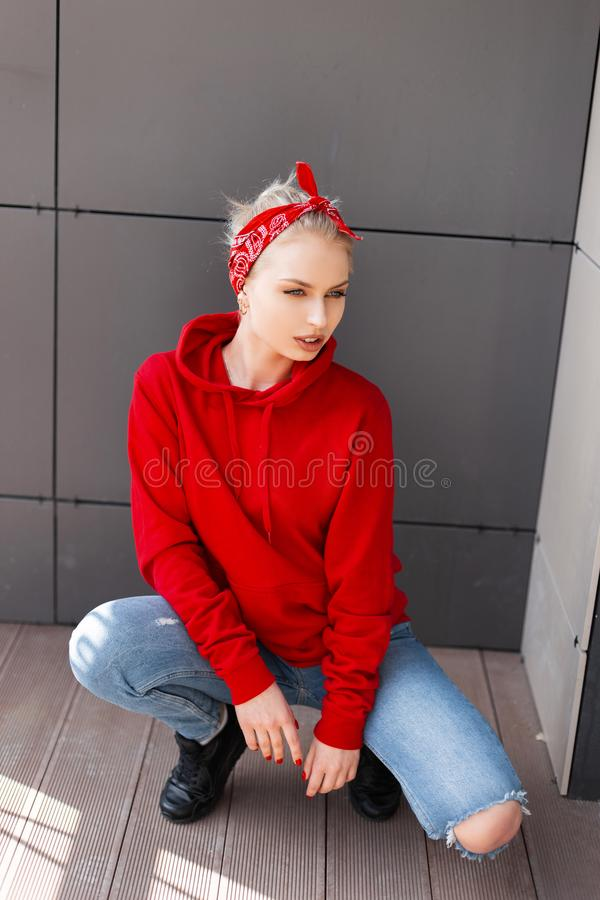 Young fashionable woman in black boots in a stylish red sweatshirt in ripped jeans with a vintage bandana sits on in the city. Near the gray wall. Attractive royalty free stock image