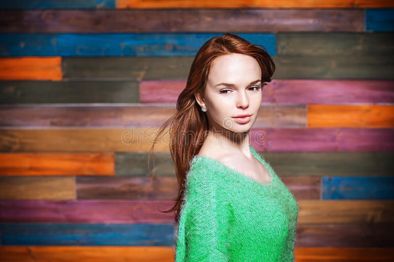Young fashionable woman with red hair. Young beautiful fashionable woman with long red hair looking to the camera over colorful background. Hairdo style royalty free stock images