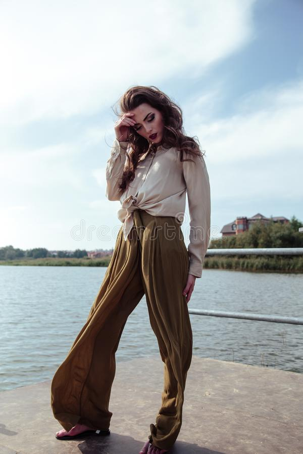 Young fashionable woman in stylish clothes posing near river side in a summer evening. Fashion model stock photo