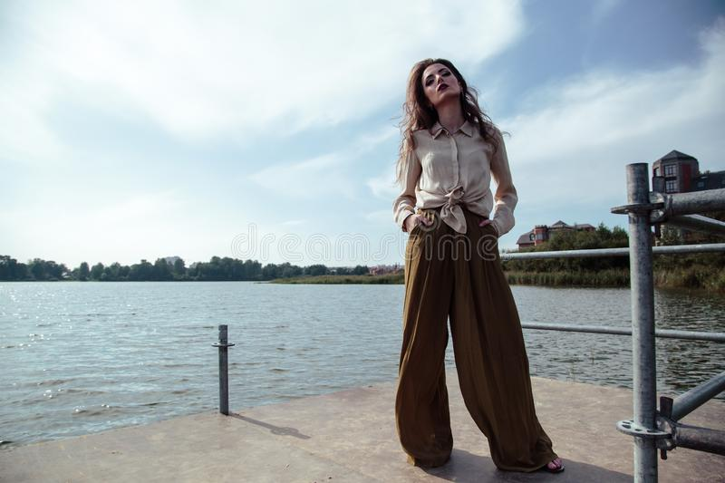 Young fashionable woman in stylish clothes posing near river side in a summer evening. Fashion model royalty free stock image