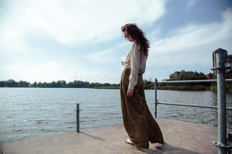 Young fashionable woman in stylish clothes posing near river side in a summer evening. Fashion model royalty free stock photos
