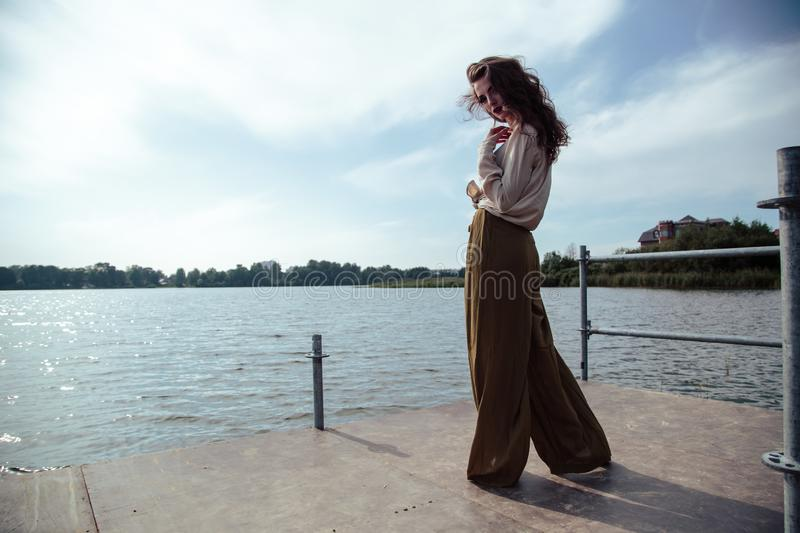 Young fashionable woman in stylish clothes posing near river side in a summer evening. Fashion model stock images