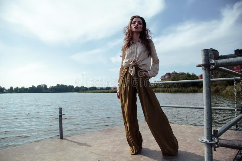 Young fashionable woman in stylish clothes posing near river side in a summer evening. Fashion model stock image