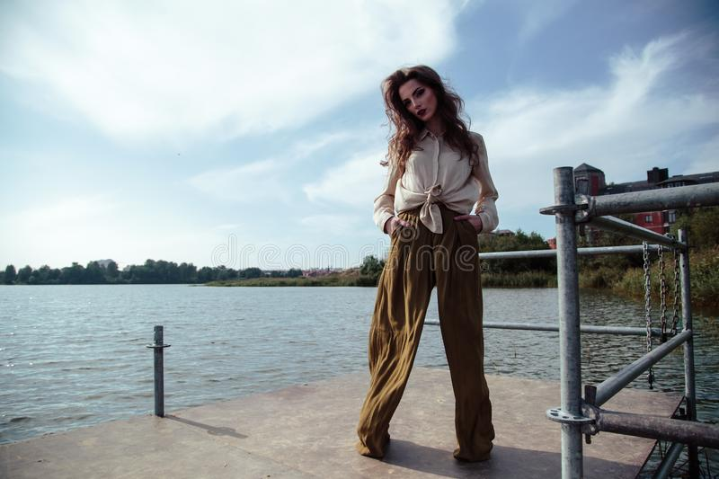 Young fashionable woman in stylish clothes posing near river side in a summer evening. Fashion model stock photos