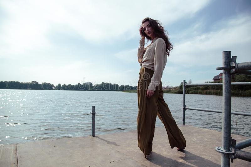 Young fashionable woman in stylish clothes posing near river side in a summer evening. Fashion model royalty free stock photo