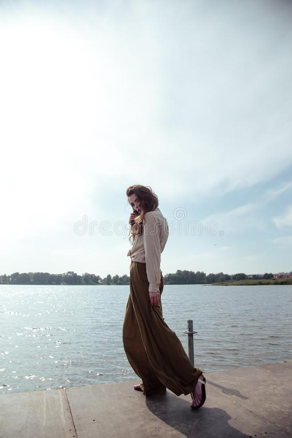 Young fashionable woman in stylish clothes posing near river side in a summer evening. Fashion model royalty free stock photography