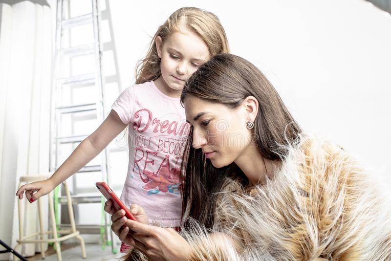 Young fashionable woman is looking into the phone with her daughter a little girl. royalty free stock photography