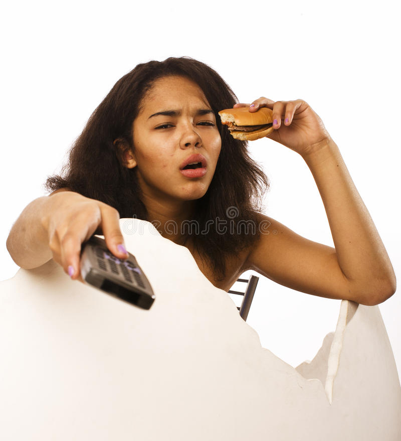Young fat african american teen girl with remote and hamburger isolated, unhealthy obsessed stock photography