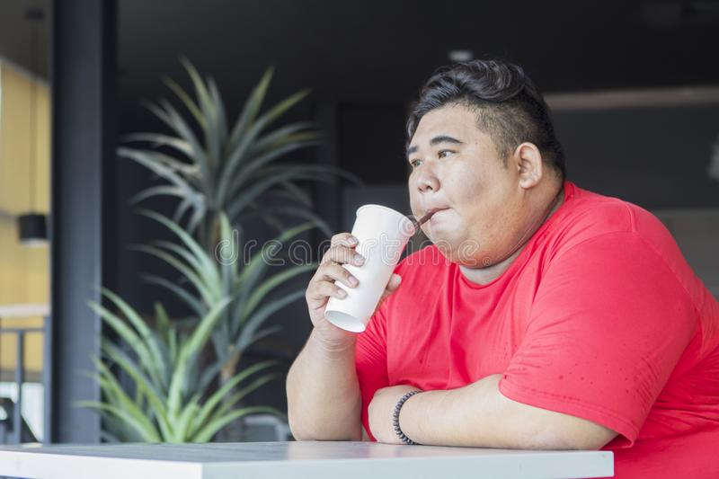 Young fat man drinking a glass of cola in the cafe. Picture of young fat man drinking a glass of cola while sitting in the cafe royalty free stock image