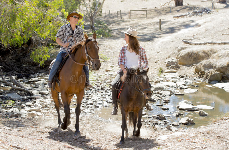 Young father as horse instructor of young teen daughter riding little pony wearing cowgirl hat. Young American Australian men as father or horse instructor of stock image
