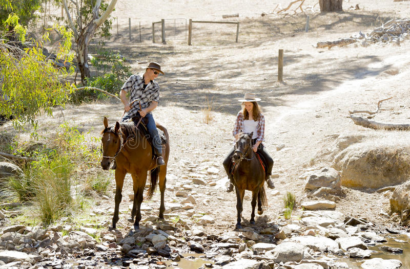 Young father as horse instructor of young teen daughter riding little pony wearing cowgirl hat. Young American Australian men as father or horse instructor of stock photography