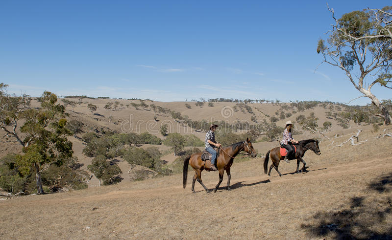 Young father as horse instructor of young teen daughter riding little pony wearing cowgirl hat. Young American Australian men as father or horse instructor of stock images