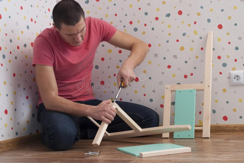 Father assembles a chair for children stock image