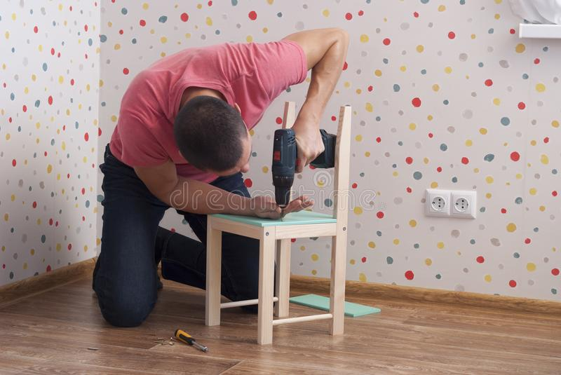 Father assembles a chair for children stock photo