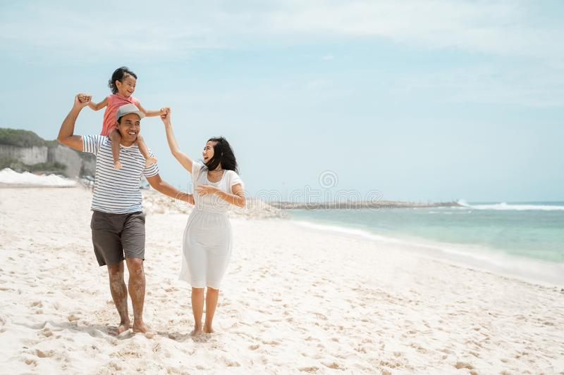 Young father carrying daughter on the shoulder when enjoy the beach with mother royalty free stock photo