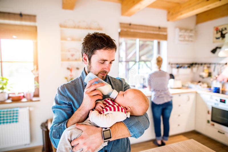 Young father carrying and feeding his newborn baby son royalty free stock image