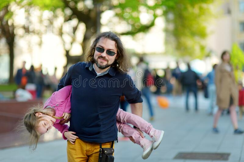 Young father carrying his adorable little daughter during summer city walk royalty free stock photography