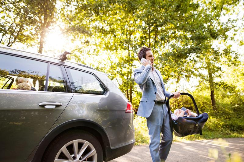 Young father with a smartphone going into the car with his baby stock images