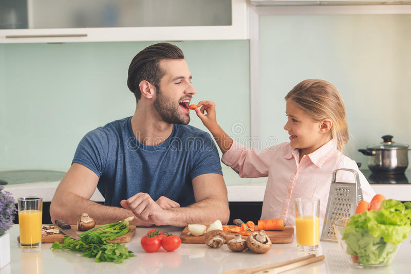 Young father and daughter cooking meal together. Young father and his daughter cooking meal together in kitchen smiling stock photo