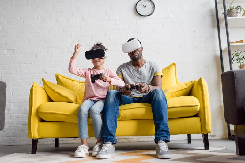 young father and daughter in vr headsets playing video games on couch stock images