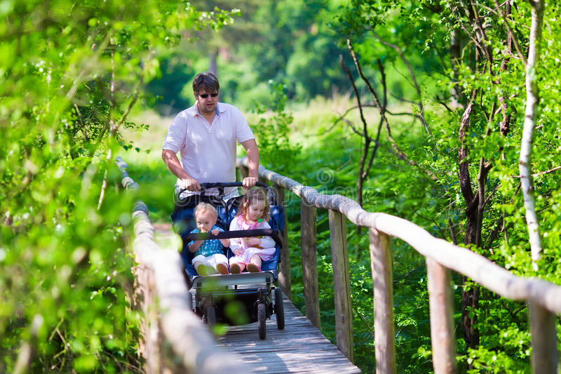 Young father with double stroller in a park royalty free stock image