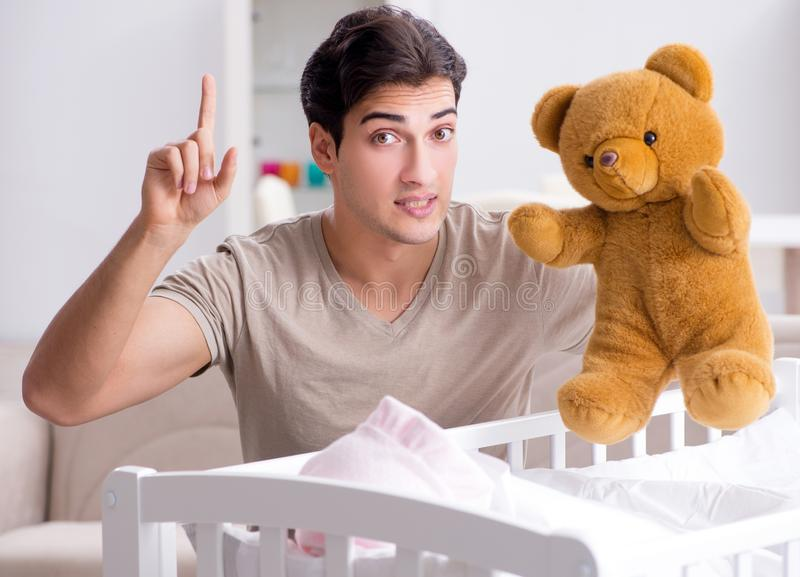 Young father enjoying time with newborn baby at home. The young father enjoying time with newborn baby at home stock image