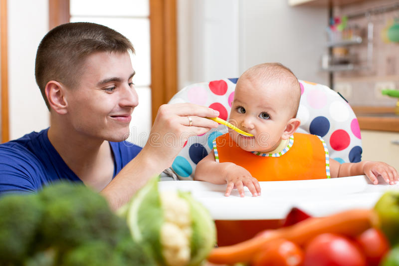 Young father feeding his baby at kitchen stock photography