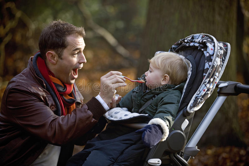 A young father feeding his son in the park royalty free stock photos