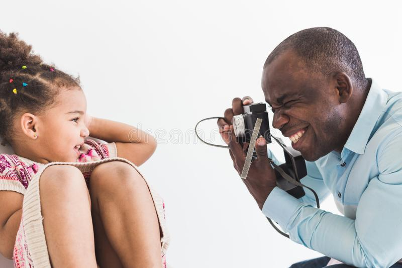 Young father with his cute little daughter taking pictures of each other on an old vintage camera stock photo