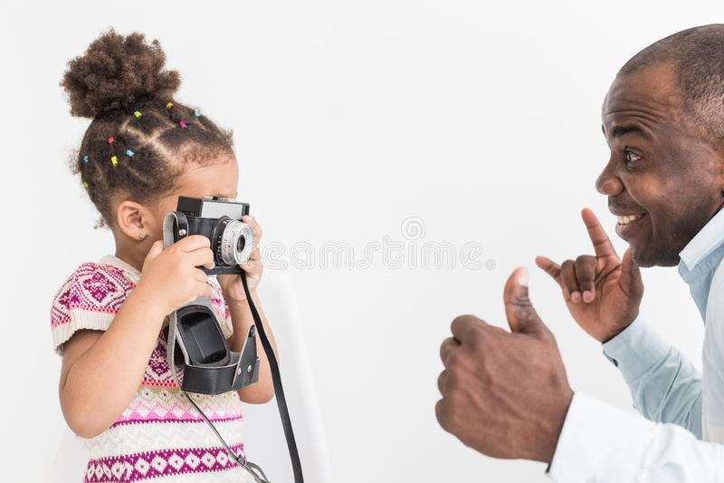 Young father with his cute little daughter taking pictures of each other on an old vintage camera royalty free stock image