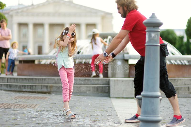 Young father and his little girl having fun with drinking water fountain on warm and sunny summer day. stock image