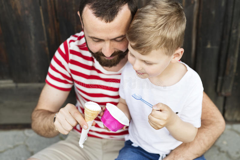 Young father and his little son eating ice cream. Sunny day. stock photo