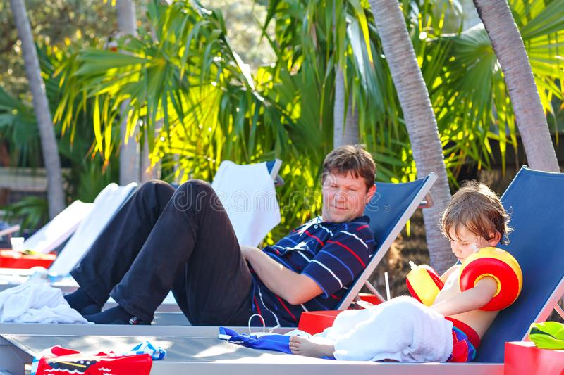 Young father and his little son resting near swimming pool. Man and little preschool kid boy in swim floaties making royalty free stock photography