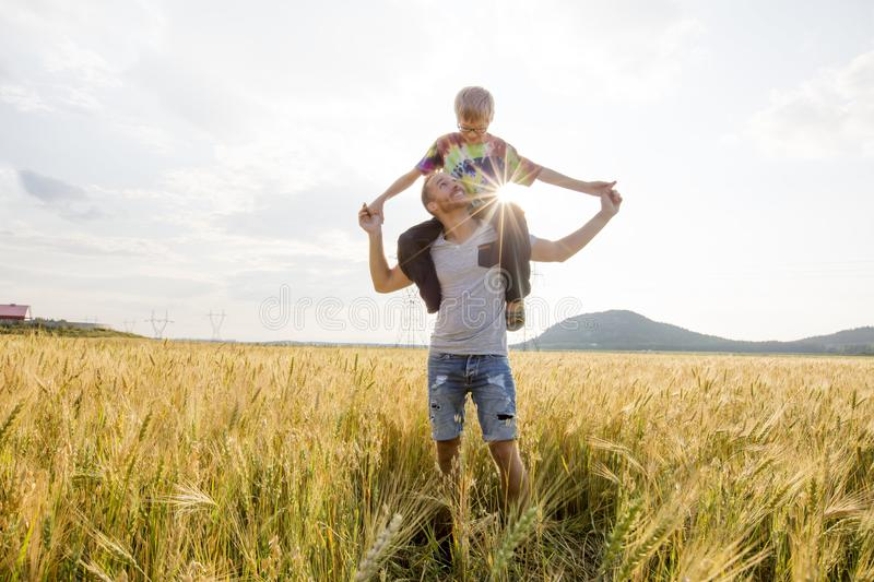 Young father with his little son walking in the wheat field at sunset in a warm summer day stock photography
