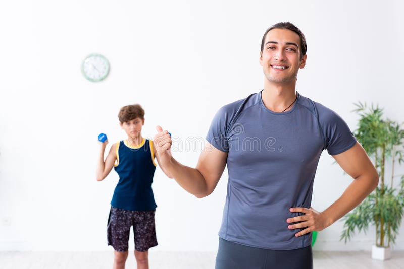 Young father and his son doing exercises. The young father and his son doing exercises royalty free stock photo