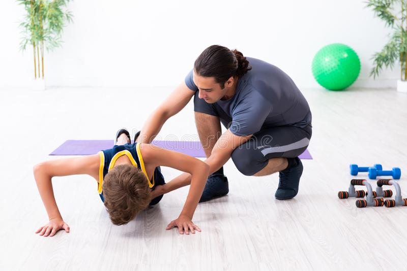 Young father and his son doing exercises. The young father and his son doing exercises royalty free stock image