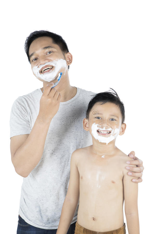 Young father and his son shaving beard stock photos
