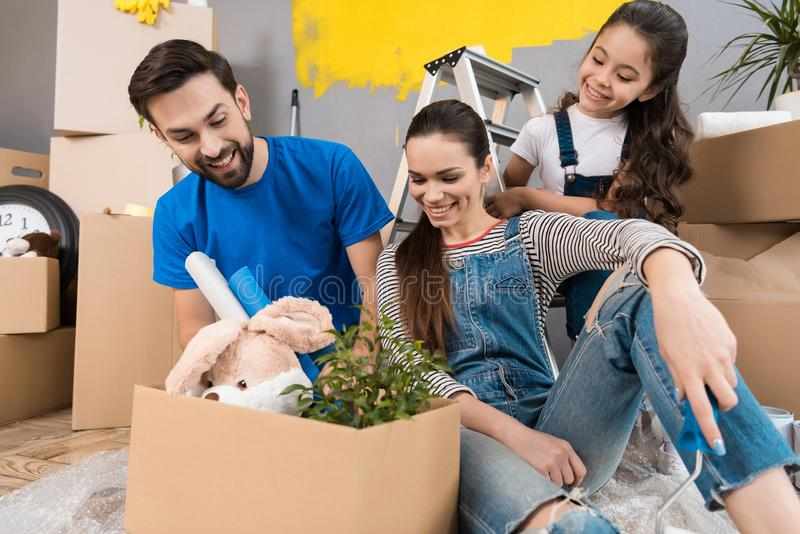 Young father and his wife and daughter sort things out from cardboard boxes in house they moved. royalty free stock photography