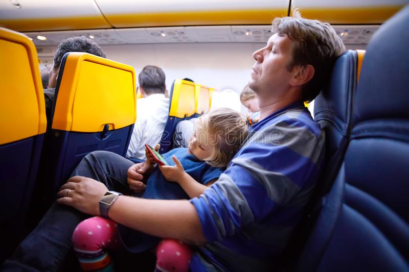 Young father holding his baby toddler daughter during flight on airplane going on vacations. Tired man and cute girl royalty free stock photos