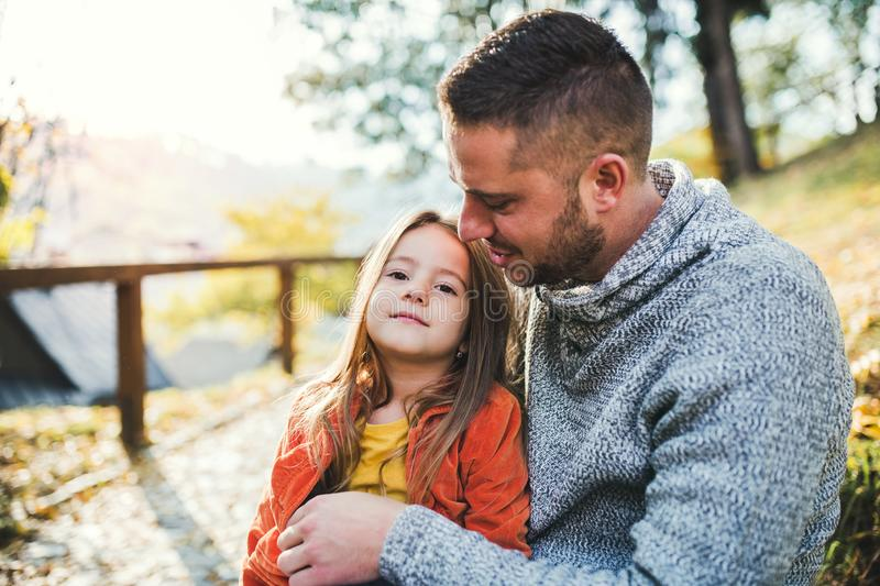 A young father with a small daughter in autumn nature, sitting. stock images