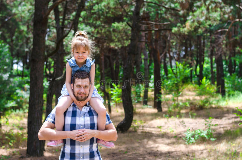 A young father holds a daughter on his shoulders, a happy family stock photography