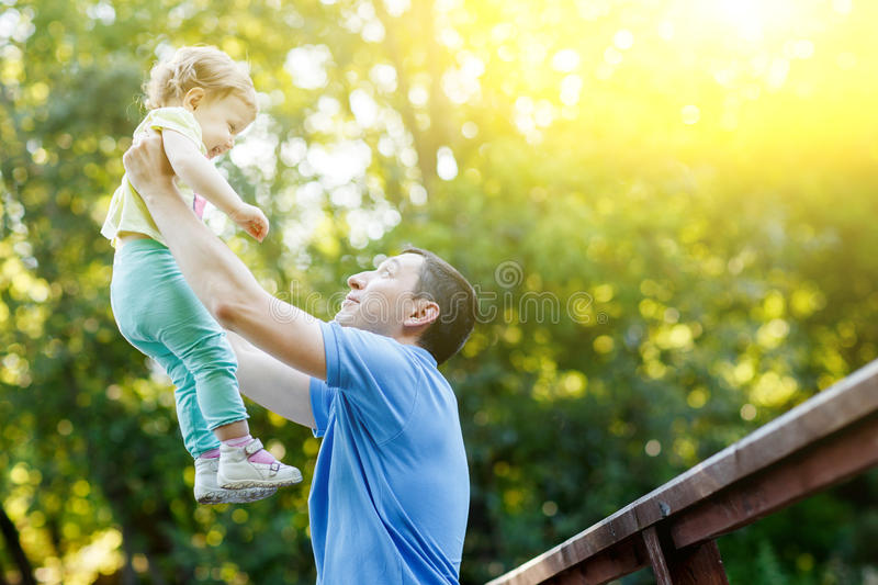 Young father holds little daughter in arms in park stock images