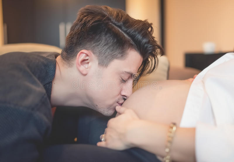 Young father kissing pregnant belly of wife. Happy family awaiting a baby royalty free stock images