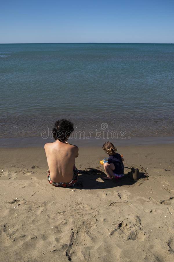 Young father and little daughter sitting on the beach and playing with sand. Back view with blue sea. Vetical shot. Marina di Grosseto, Tuscany, Italy royalty free stock image