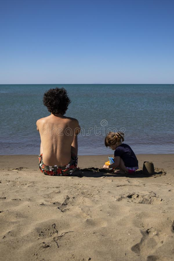 Young father and little daughter sitting on the beach and playing with sand. Back view with blue sea. Vetical shot. Marina di Grosseto, Tuscany, Italy stock photo