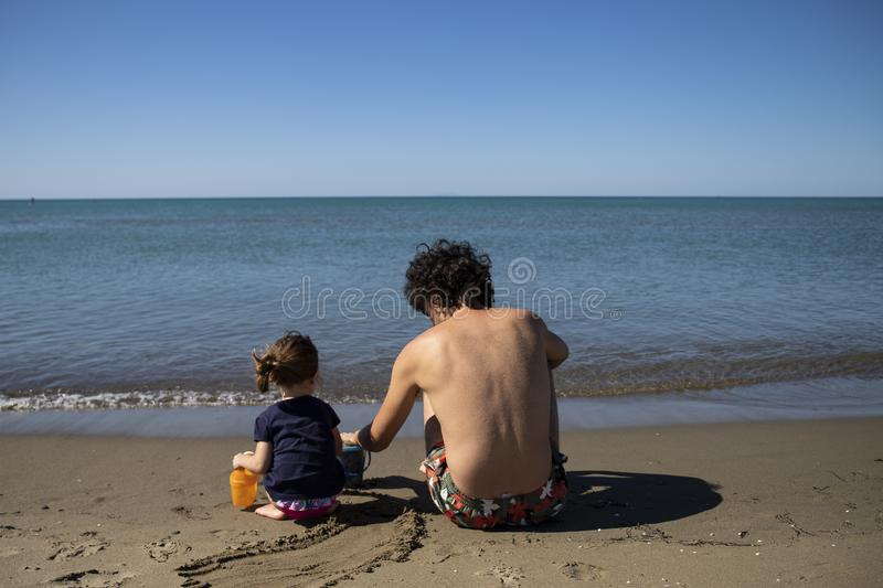 Young father and little daughter sitting on the beach and playing with sand stock photos