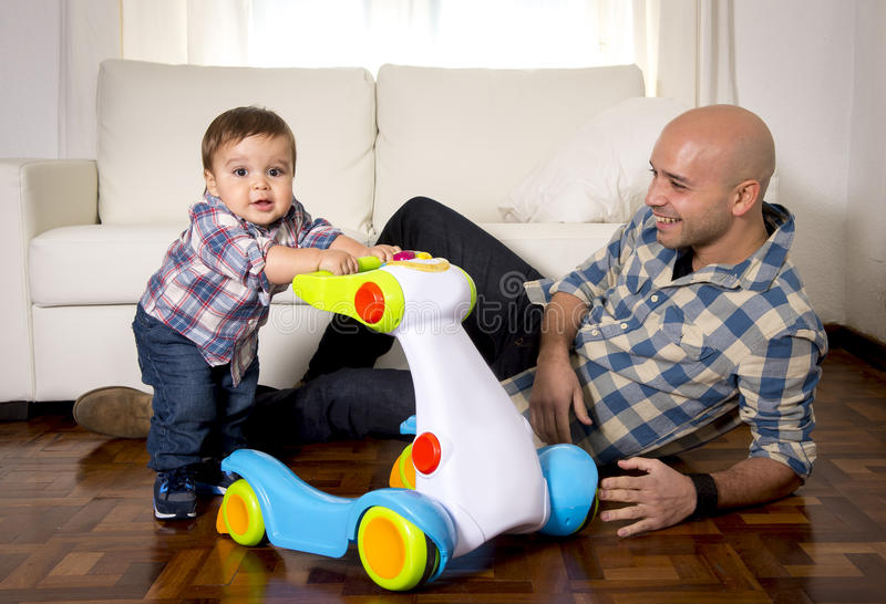Young father and little son walking with baby walker taking his first brave steps royalty free stock image